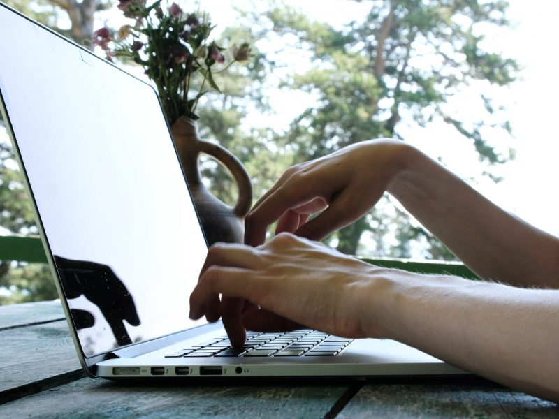Woman typing on a laptop outdoors in summer close-up. Teleworking, communication on the Internet or education by nature.